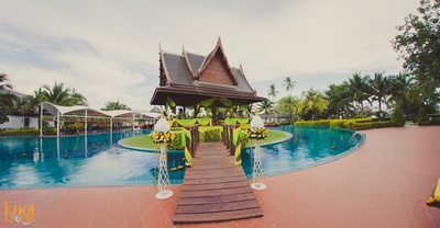 Pool side area at Sofitel, Krabi decorated with two-toned yellow and green drapes and floral stand alones