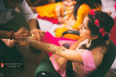 Floral head gear, bride is dressed in all pink for her mehendi ceremony
