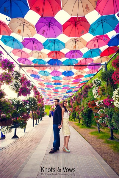 Dressed in sharp outfits for the pre wedding photo shoot under a umbrella canopy with clustered seasonal flowers around it