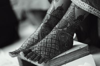 Detailed mehendi patterns designed on the brides feet