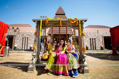 Bride and her family sitting on a jhoola decorated with yellow and orange marigold flowers