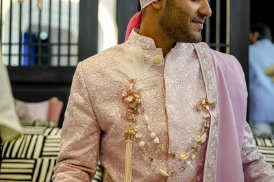the groom in a pink sherwani and a unique brooch for the wedding