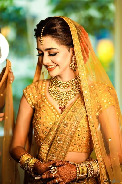 the beautiful bride in golden-yellow lehenga for her wedding