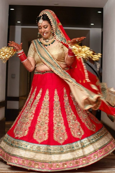 Red wedding lehenga embellished with embroidered thread work motifs embellished with beads, sequins and stones