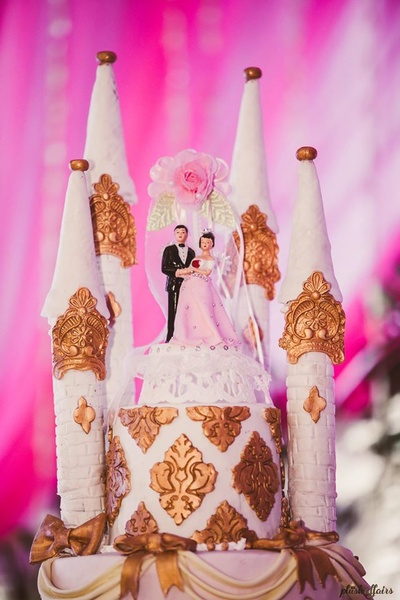 Dreamy Castle Wedding cake topped with bride and groom for the engagement ceremony.