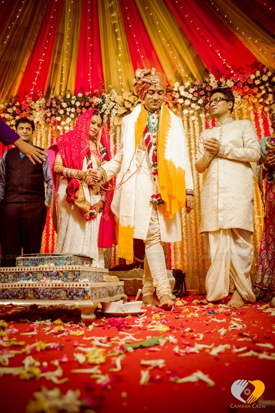 Vedi mandap decorated in red and yellow drapes with series lights, clustered floral arrangement and Jasmine strings