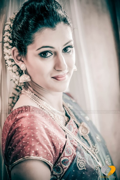 Bride is wearing blue blouse emeblllished with gold threadwork and stone work styled with red raw silk blouse
