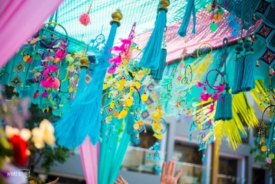 Stunning ceiling decor idea of vibrant pink, yellow and blue dreamcatchers and tassels!