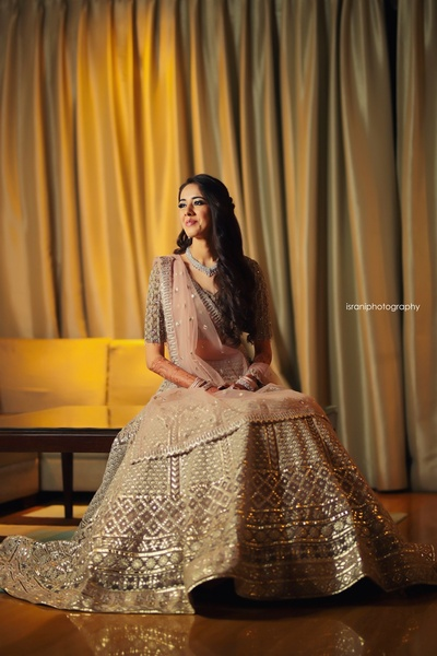 The bride looking radiant in a ivory and blush lehenga for her sangeet