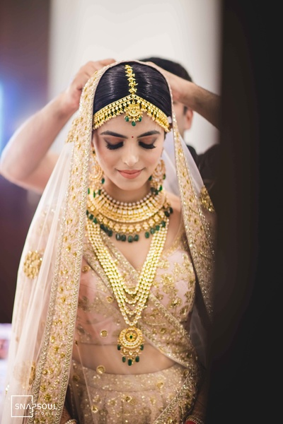 The bride is slaying it in this light pink and gold lehenga with contrasting gold and emerald jewellery!