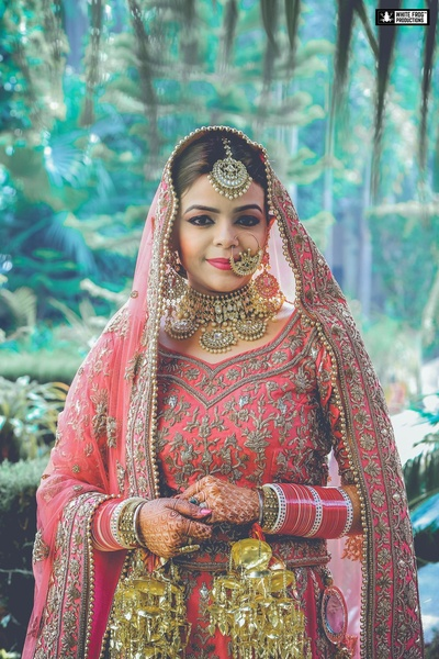 Bride with flawless rosy make up in an embroidered pink lehenga