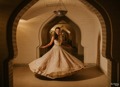 the bride twirling in her cream lehenga at her sangeet ceremony