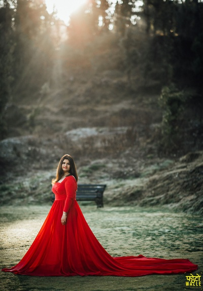 The bride looks absolutely drool-worthy in this eloquent red gown with a long trail.