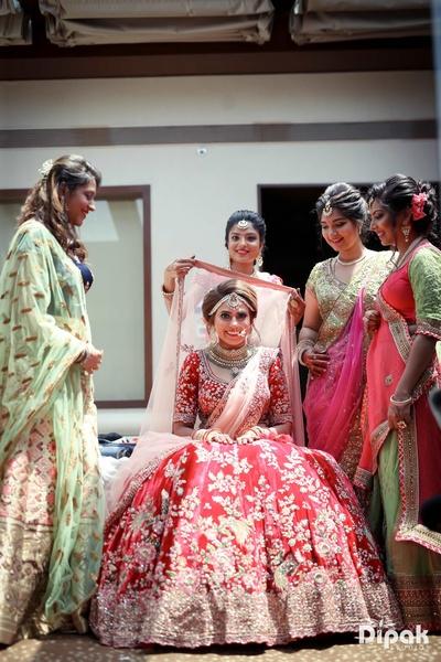 Bridesmaids helping the bride get ready for the wedding function at Sahar Star, Mumbai