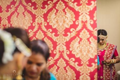 Fuchsia and red bridal lehenga by Sabysachi Mukherjee, styled with kundan and meenakari studded gold layered jewellery by Diva Creations and Sunil Jewllers