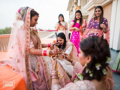 Bride captured in a candid shot with her bridesmaids while getting ready for the wedding ceremony