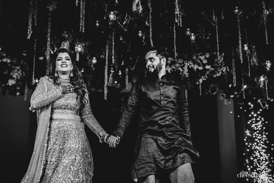 A black and white candid picture of the couple at the sangeet