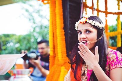 Bride wearing minimal makeup and minimal floral jewellery with a beautiful gold and kundan nose ring.