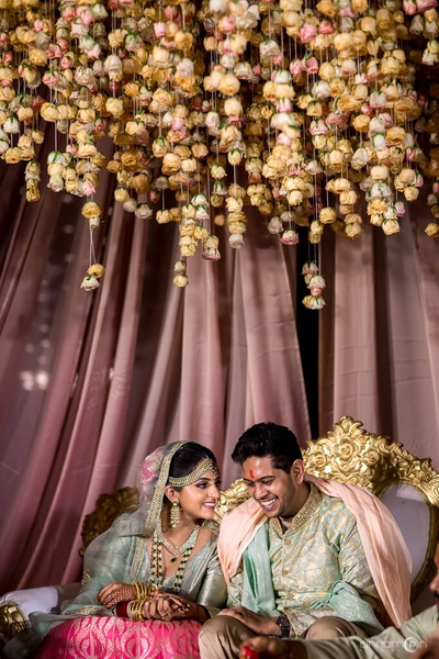 Candid capture of the bride and groom at the floral mandap
