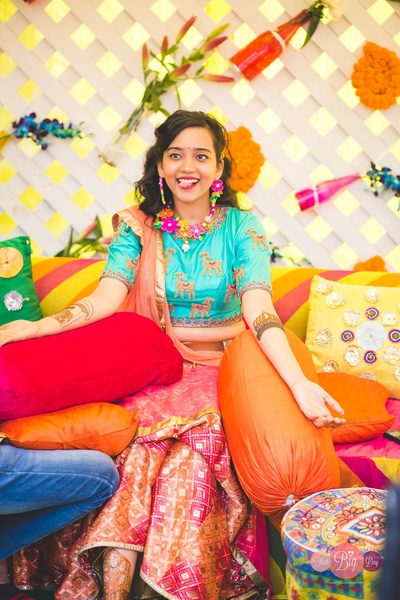 Ritika wearing a bright and colourful outfit for her Mehendi ceremony.