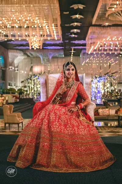 The bride looks like a million bucks in her red traditional lehenga, paired with gold and emerald jewellery.