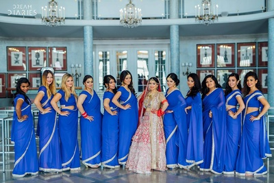 Bridesmaids dressed up in coordinated plain blue sarees with silver border. Complementing the bride in a unique way.
