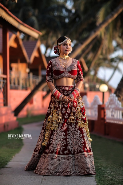 The bride looks stellar in this opulent maroon emebellished lehenga, with large kaleeras and dramatic jewellery!