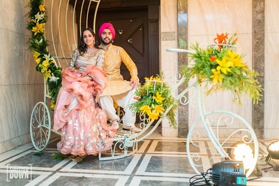 the bride and groom striking a pose on a  decorated cycle at a pre wedding function