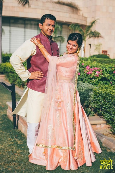 Sid wearing maroon bandhgala with off white kurta and pajama complementing Rupa in Pastel pink silk lehenga with minimal embroidery work