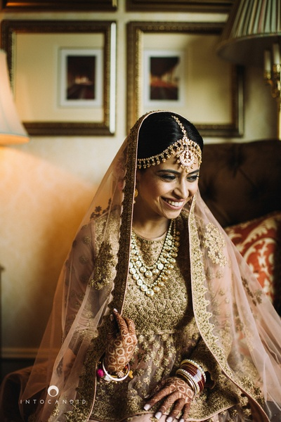 Wearing beige and baby pink bridal lehenga with heave gold embroidery styled with polki neck piece and polki mattha patti.