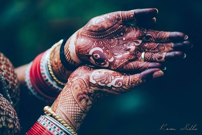 Hands covered in bridal mehendi design and the groom's name