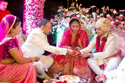 Pink flared bridal lehenga embellished with gold sequined motifs by Sabyasachi Mukherjee