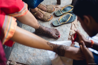 Bridal feet covered in intricately patterned swirls and paisleys mehendi designs