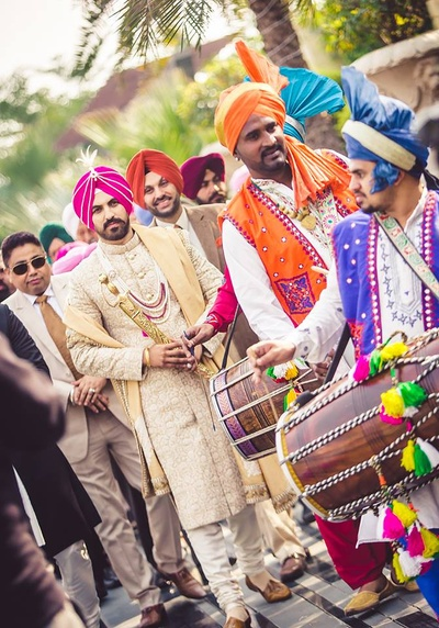 Colorful and bright baraatis entering the wedding venue with dhol and nagadas for the wedding ceremony.