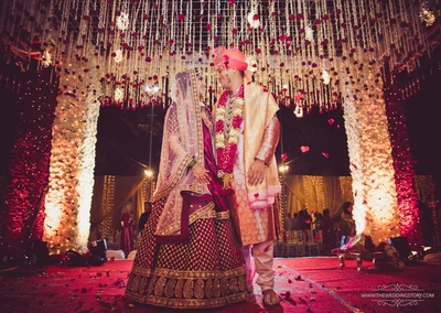 Bride and groom post at the mandap in their bridal lehenga and embroidered sherwani