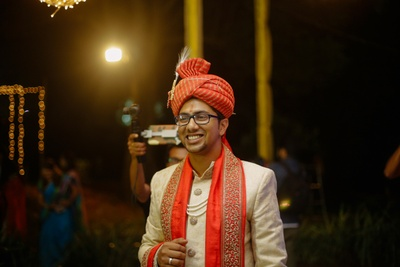 Groom wearing white sherwani with red dupatta and red turban on his wedding  held at Elements, Bangalore.