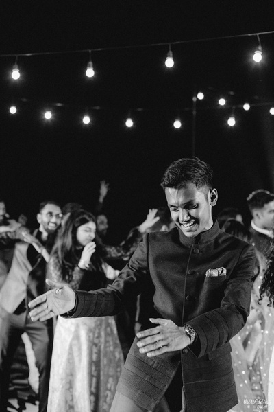 a black and white candid capture of the groom dancing at the sangeet