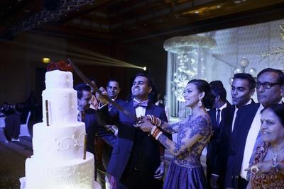 Cutting the big white wedding cake.