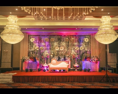 Sangeet setup with a diwan, chandelier lighting and clustered floral arrangement
