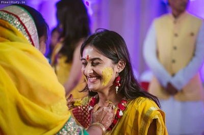 Khushboo dressed up in a haldi yellow saree and red brocade blouse, styled with minimal floral jewellery for the Haldi Ceremony.