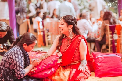 a candid capture of the bride while she gets mehendi on her hands