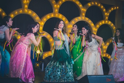 the bride and bridesmaids dance performance at the sangeet