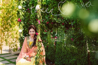 The bride sitting in a yellow lehenga against a floral backdrop