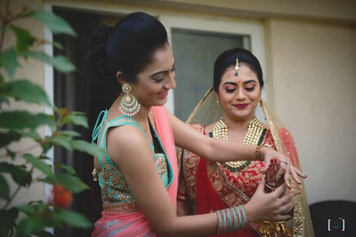 The traditional bride gets ready for her big event in a red and gold Meena bazaar lehenga