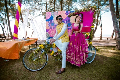 Bride and groom posing with the quirky decor set up at The Lalit Golf and Spa Resort, Goa for the mehndi function