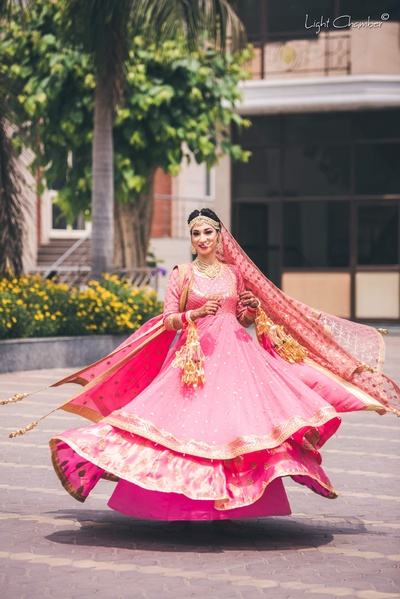 Traditional bride twirling in her pink lehenga for the wedding at GK 1 Gurudwara