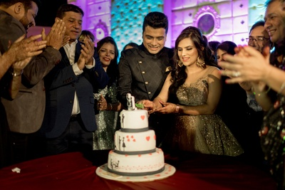 The couple cutting a beautiful three-tier cake.