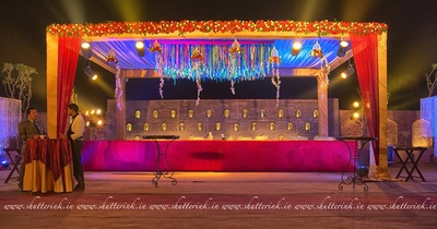 Wedding venue lit up by dramatic lightings, floral chams, clustered wall bouquet and stringed chandelier