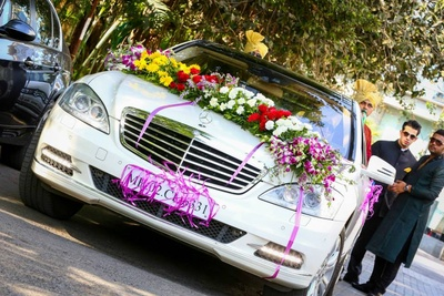 Wedding car decorated with clustered floral arrangement and ribbons