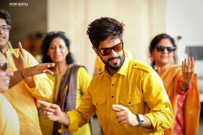 candid picture of the groom dancing at his haldi ceremony